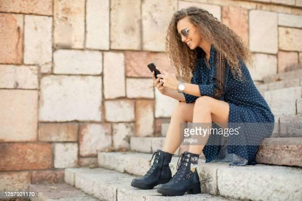 mooie jonge vrouwenzitting op treden - laars stockfoto's en -beelden