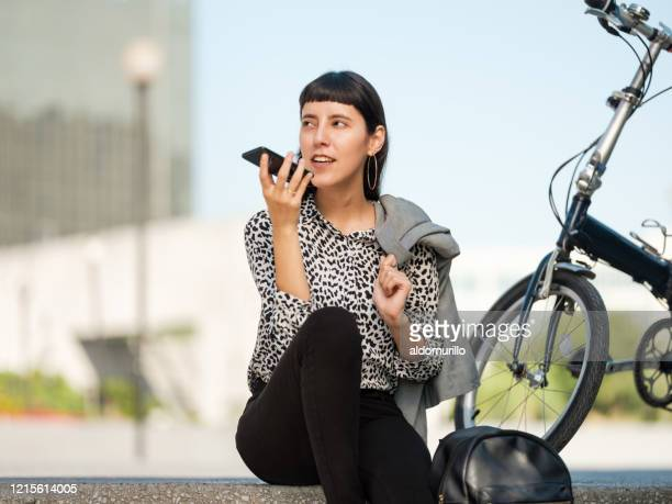 beautiful young  woman sitting outside and talking on phone - medium shot stock pictures, royalty-free photos & images