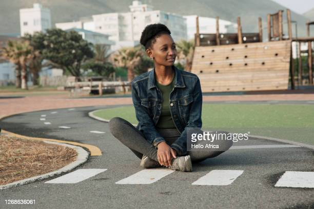 beautiful young woman sitting patiently at a miniature pedestrian crossing - one young woman only stock pictures, royalty-free photos & images