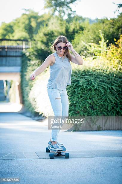 Beautiful young woman skateboarding in the city