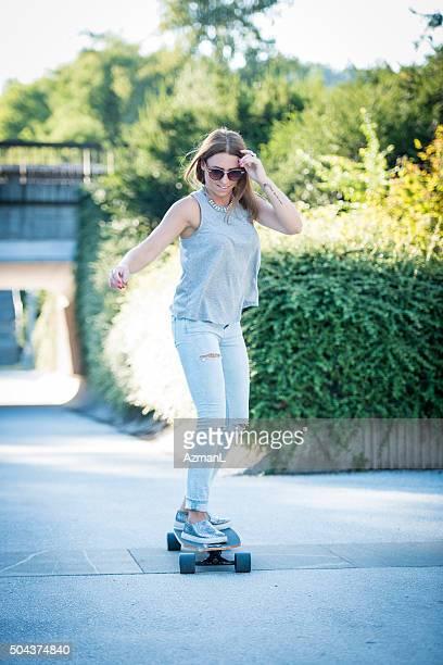 Hermosa mujer joven skateboarding en la ciudad