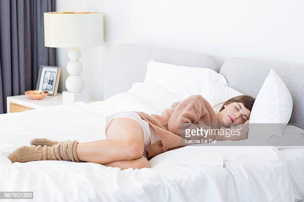 beautiful young woman sleeping on the bed - lying on side stock pictures, royalty-free photos & images