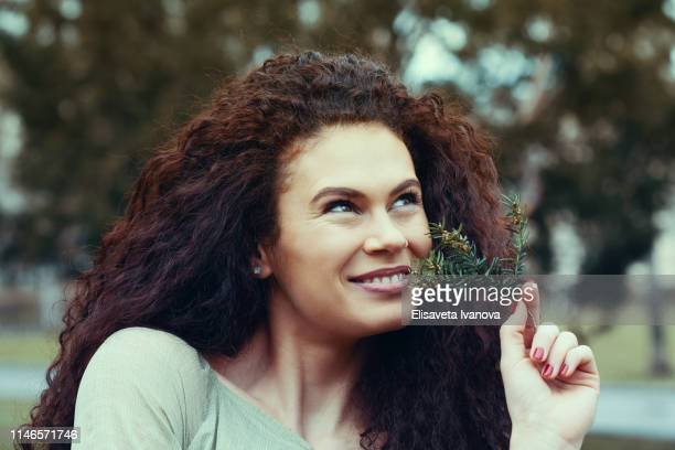 Beautiful young woman smelling the scent of a twig