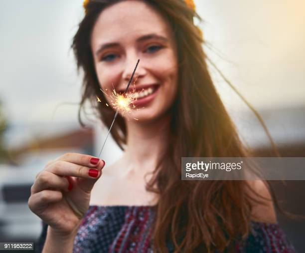 Beautiful young woman smiles, holding burning sparkler firework