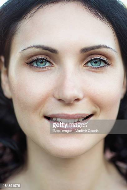 A beautiful young woman smiling into the camera, close-up of face