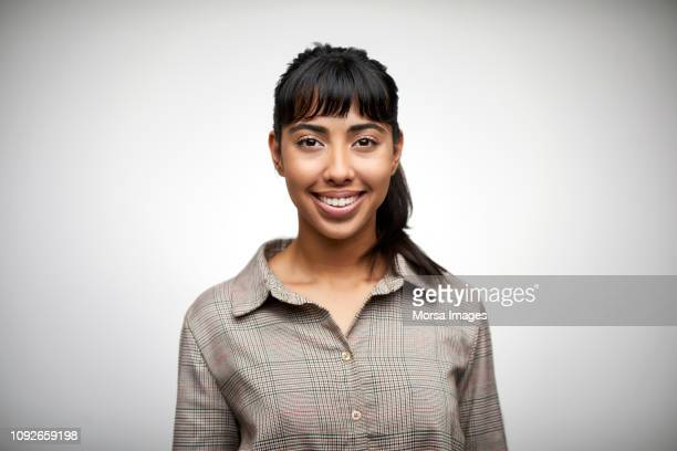 beautiful young woman smiling on white background - latino américain photos et images de collection