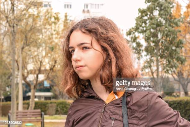 beautiful young woman standing against tree - junior girl models stock pictures, royalty-free photos & images