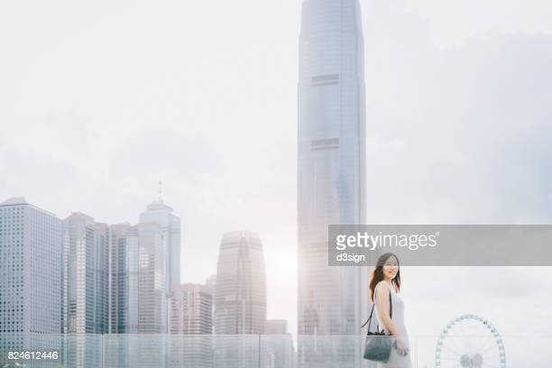 Beautiful young woman standing against urban city skyline in a fresh morning