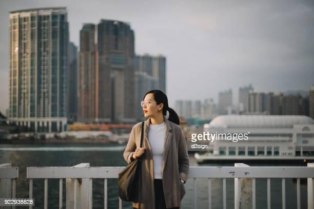 beautiful young woman standing at a pier overlooking hong kong's modern skyline - victoria harbour hong kong stockfoto's en -beelden