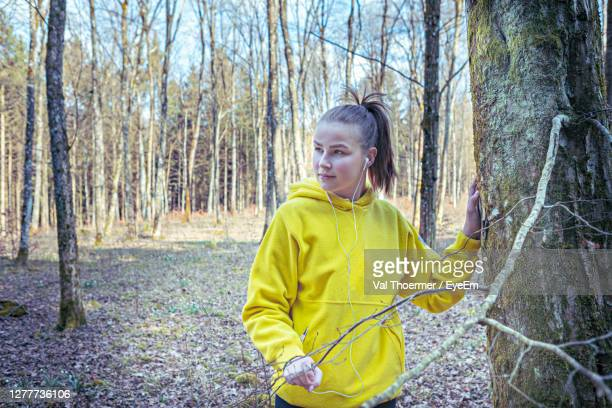 beautiful young woman standing by tree trunk in forest - val thoermer stock-fotos und bilder