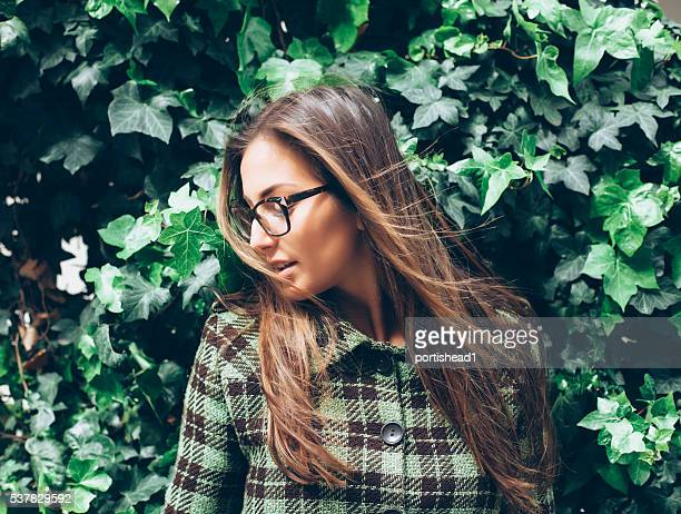 beautiful young woman standing in front of an ivy wall - green coat stock pictures, royalty-free photos & images