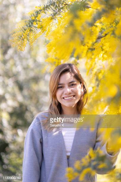 beautiful young woman standing in mimosa trees - mimosa foto e immagini stock