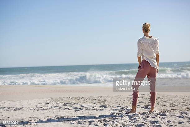 Beautiful young woman standing on sunny beach