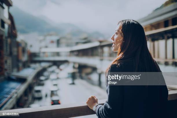 beautiful young woman standing on terrace looking at view with sunlight shining on - 観光客 ストックフォトと画像