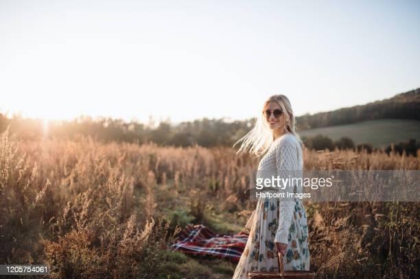 beautiful young woman standing outdoors in autumn nature at sunset. - rok stockfoto's en -beelden