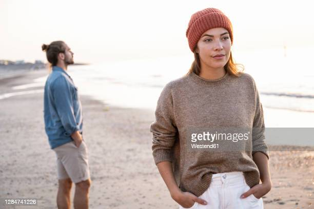 beautiful young woman standing with hands in pockets against boyfriend at beach during sunset - 不満 ストックフォトと画像
