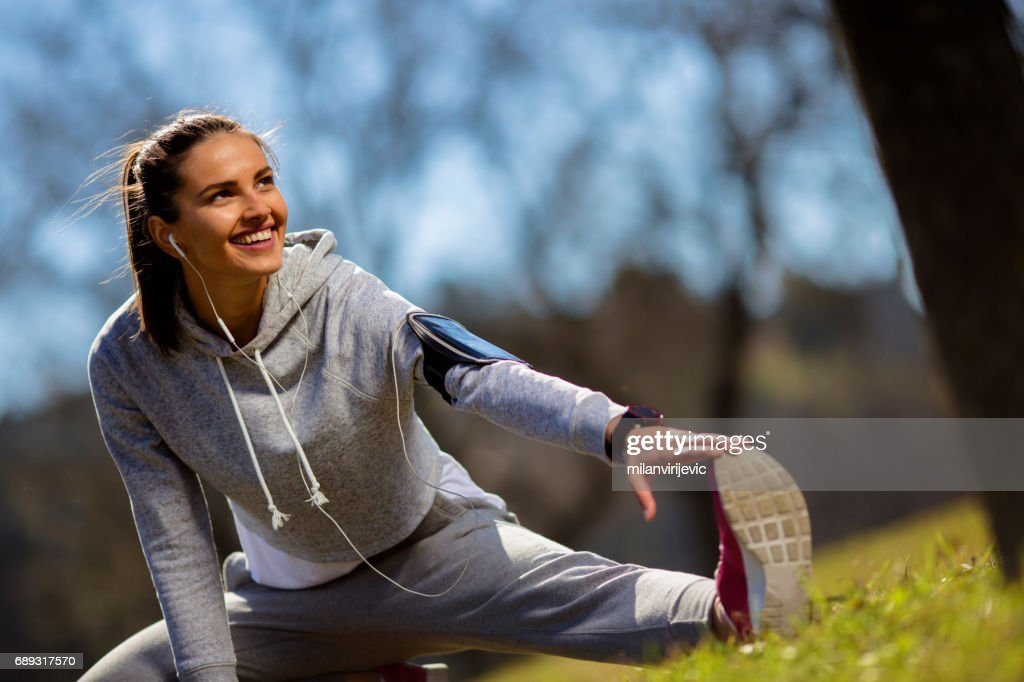 Beautiful young woman stretching in nature : Stock Photo