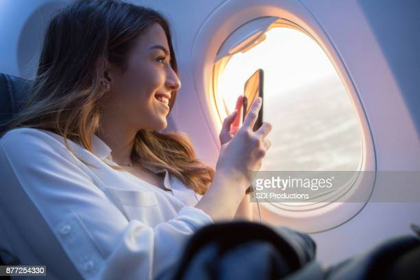 beautiful young woman takes sunset picture from airplane - aeroplane stock pictures, royalty-free photos & images