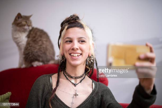 beautiful young woman taking a selfie with her cute selkirk rex cat - north holland stock pictures, royalty-free photos & images