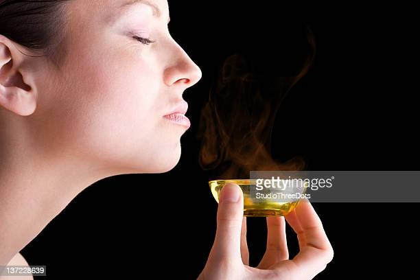 Beautiful young woman taking aroma therapy