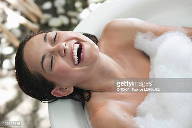 Beautiful young woman taking bubble bath and smiling