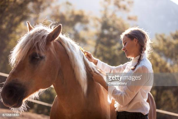 Beautiful Young Woman Taking Care of her Horse