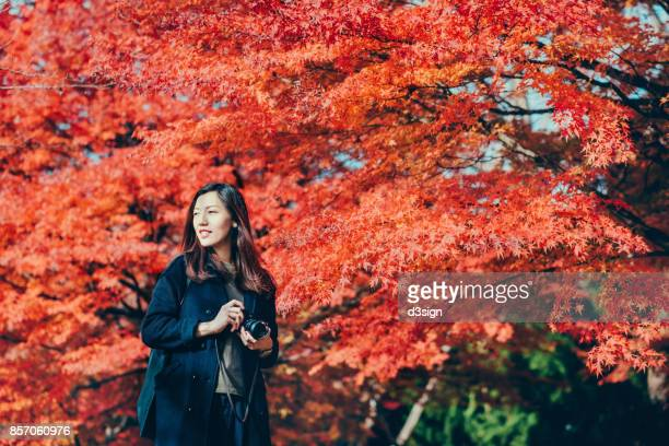 Beautiful young woman taking photos in park against red maple in Autumn