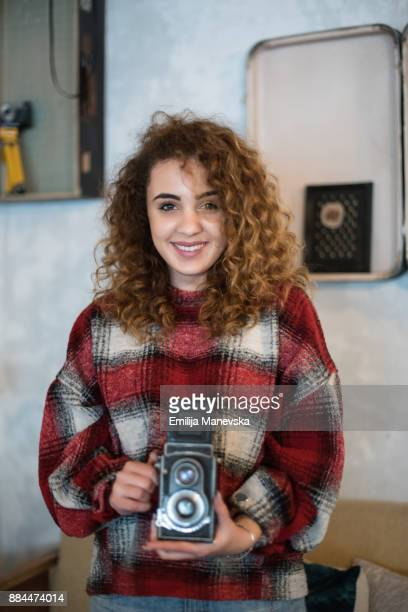 Beautiful young woman taking photos with vintage camera