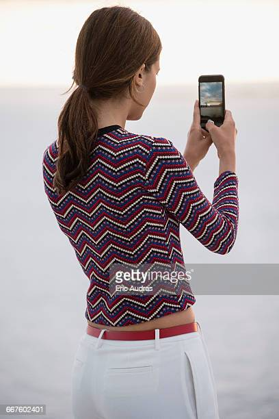 beautiful young woman taking picture with camera phone at riverbank - photographing stock pictures, royalty-free photos & images