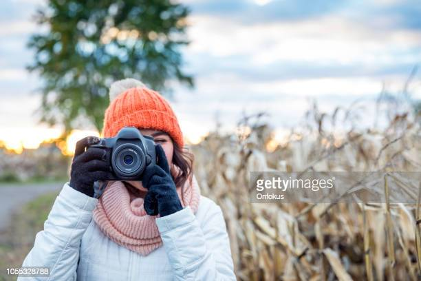 beautiful young woman taking picture with digital camera at sunset - novembre foto e immagini stock