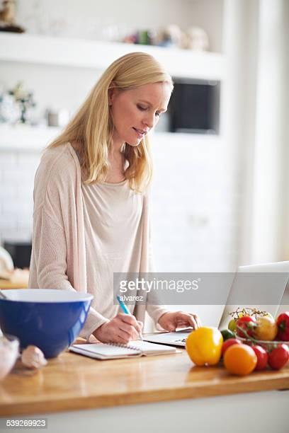 schöne junge frau mit rezept aus internet - food journal stock-fotos und bilder