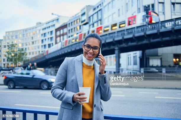 beautiful young woman talking on her smartphone in the city