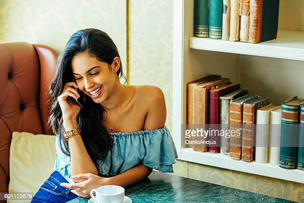 beautiful young woman talking on the phone in a bar - bar drink establishment stock pictures, royalty-free photos & images
