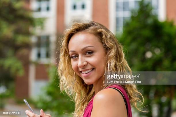 A beautiful young woman texting on her smart phone on a university campus and pausing to look at the camera