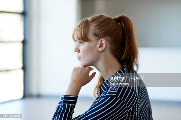 beautiful young woman thinking while looking away - ponytail stock pictures, royalty-free photos & images