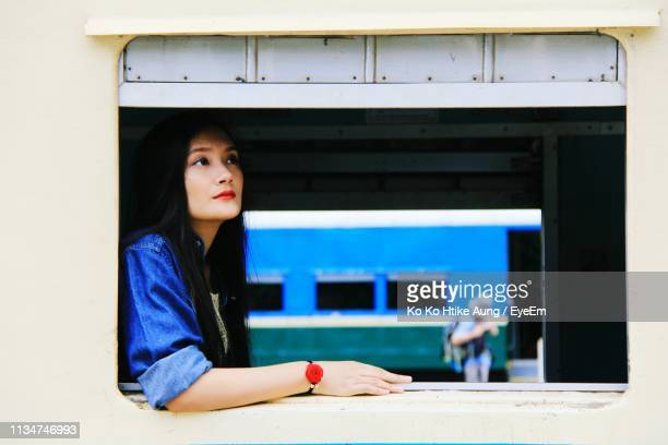 beautiful young woman through train window - ko ko htike aung stock pictures, royalty-free photos & images