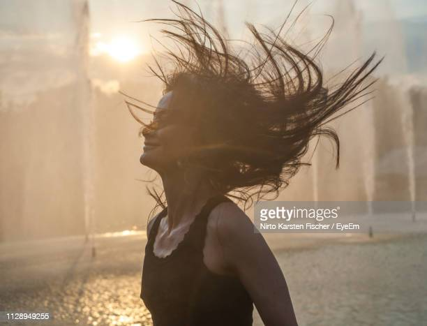 beautiful young woman tossing hair by fountain during sunset - fountain stock pictures, royalty-free photos & images