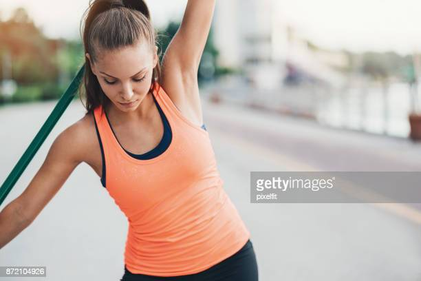 Beautiful young woman training with a resistance band