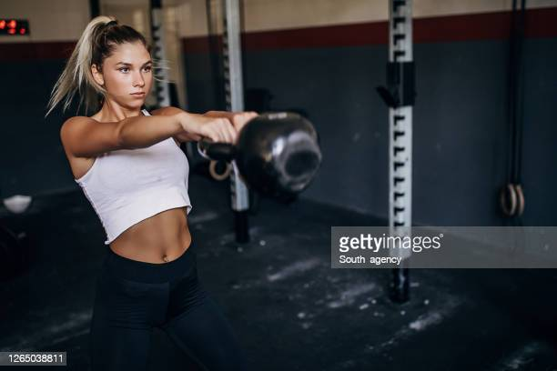 beautiful young woman training with kettlebell in gym - practicing stock pictures, royalty-free photos & images