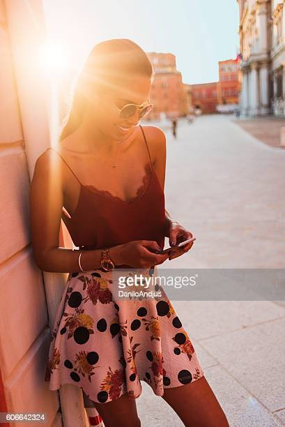 beautiful young woman typing a message on her smart phone