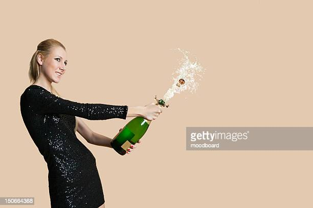 beautiful young woman uncorking champagne bottle over colored background - cocktail dress stock pictures, royalty-free photos & images