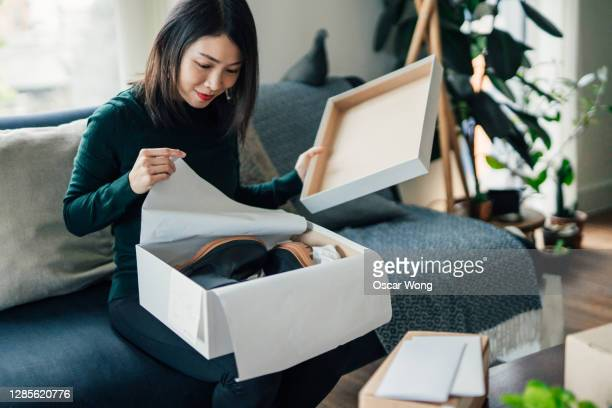 beautiful young woman unwrapping package at home - buying stock pictures, royalty-free photos & images