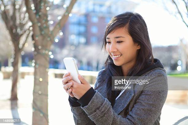 beautiful young woman uses smartphone in park - beautiful japanese girls stock photos and pictures