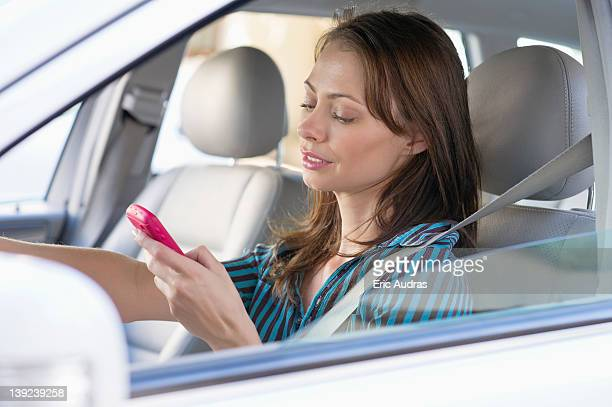 Beautiful young woman using a mobile phone while driving a car
