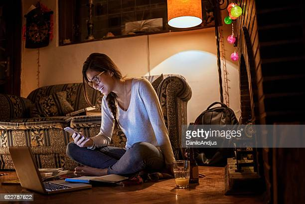 beautiful young woman using her smartphone in her cozy room