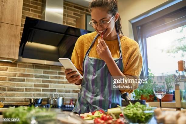 mulher jovem e bonita usando seu smartphone enquanto cozinha - cozinhando - fotografias e filmes do acervo