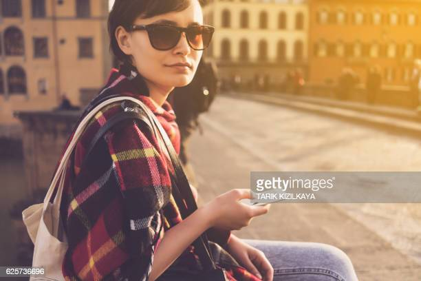 Beautiful young woman using mobile phone in the city