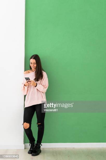 beautiful young woman using mobile phone while standing against green wall - leaning stock pictures, royalty-free photos & images