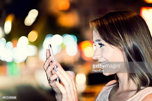 Belle jeune femme à l'aide de téléphone à côté de lumières scintillantes