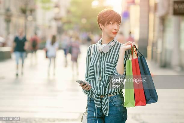 Schöne Junge Frau mit Smartphone auf der Straße